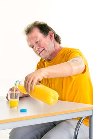 bionic: Middle-aged man with disability pouring natural orange juice from a bottle by using a bionic prosthetic left hand while sitting at a table, with copy space on white Stock Photo
