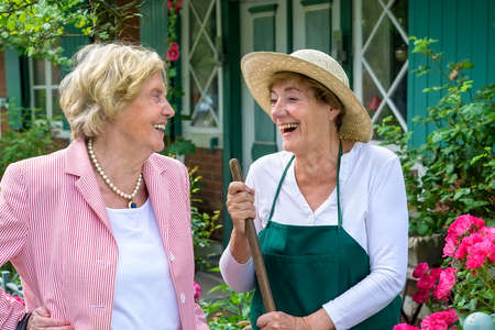 Waist Up of Two Senior Women Having Enjoyable Conversation and Laughing in Home Garden on Summer Day Stock Photo