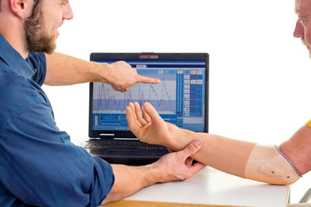 seeks: Man with prosthetic arm seeks help from technician who uses a computer seated at table against a white background Stock Photo