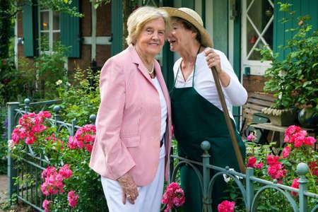 Three Quarter Length of Two Smiling Senior Women Telling Secrets in Home Garden on Sunny Summer Day