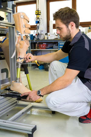 amputation: Young bearded man working on shin and knee section on prosthetic leg assembly in laboratory for research and development