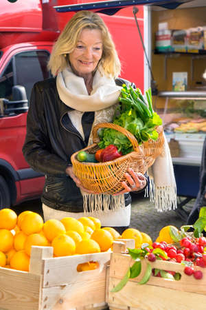 cream colored: Woman at farmers market with basket of vegetables while wearing leather jacket and long cream colored scarf