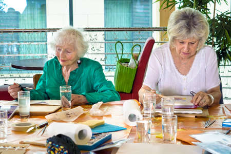 Two adorable senior women painting at table crowded with art supplies in spacious room Stock Photo