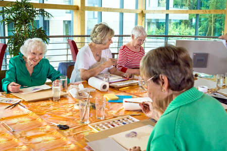 oldage: Group of four female cheerful older students painting together at table in spacious room with large windows
