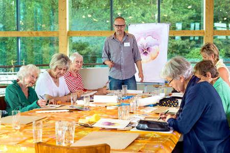 Groupe de six personnes âgées de sexe féminin à longue table en cours de peinture avec le professeur mâle dans des verres debout près devant