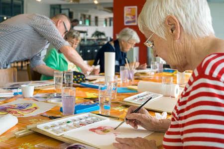 Vrouw in gestreept rood en wit overhemd die aan waterverf schildert aan tafel met andere studenten in ruime studio werken