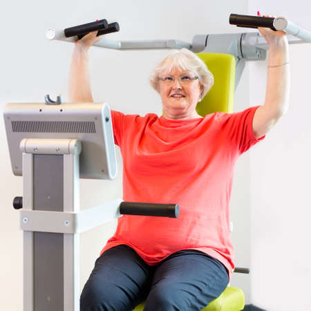 body toning: Smiling single senior woman using shoulder machine to improve upper body strength in fitness area