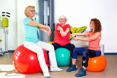 pacjent: Pair of patients with instructor stretching wrist and forearm muscles while seated on stability balance balls
