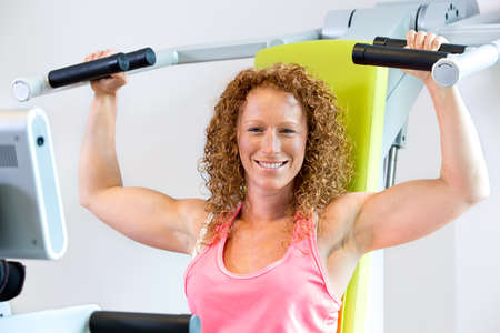 strengthening: Cheerful athletic female in red curly hair and pink top with arms in the lowered position with shoulder strengthening machine Stock Photo