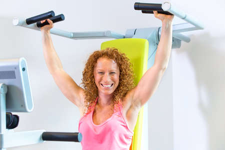 strengthening: Motivated athletic female in red curly hair and pink top with arms in the raised position with shoulder strengthening machine Stock Photo