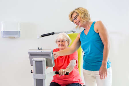 readout: Friendly female trainer in eyeglasses and blue shirt helping senior patient with settings on exercise machine Stock Photo
