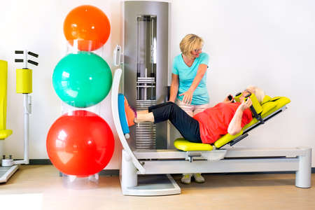 strengthening: Side view on single senior woman doing leg strengthening exercises in gym with help from physical therapist Stock Photo