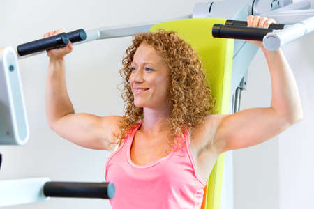 strengthening: Smiling fit woman with curly hair with arms in the raised position with shoulder strengthening machine Stock Photo