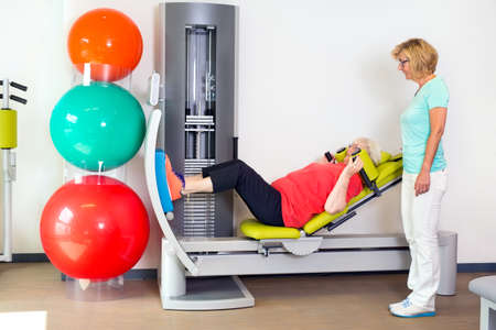 paramedical: Woman helping patient strengthen her leg muscles on large machine with sliding padded seat in gym