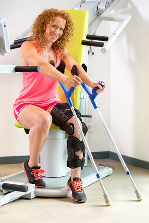 strapped: Cheerful single young adult female patient using crutches and orthopedic brace while stepping off of exercise machine Stock Photo