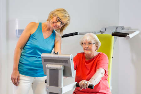 readout: Friendly female instructor in eyeglasses and blue shirt helping senior woman with exercise machine Stock Photo