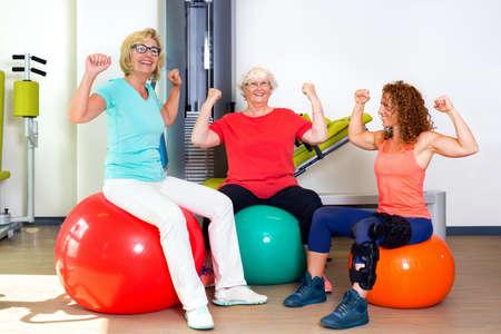 pacientes: Par de pacientes femeninos felices y músculos entrenador flexión de bíceps para mostrar su fuerza y ??confianza