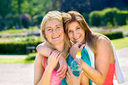 Two beautiful adult female athlete friends with towels and water bottle embracing outside after exercising