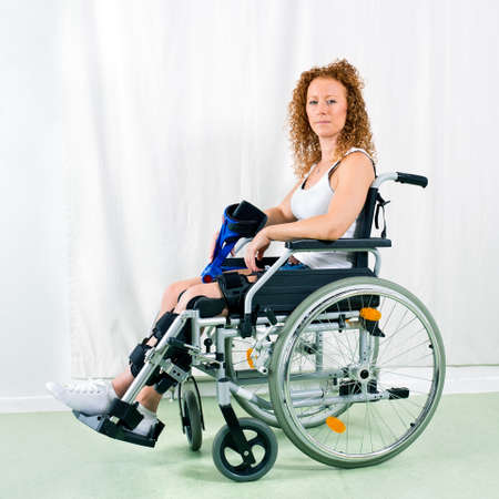 recuperation: Serious woman in wheelchair looks at camera near white canvas and wearing sleeveless shirt