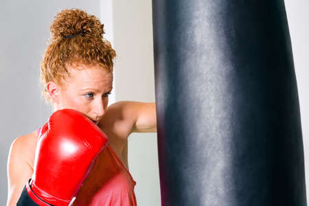 punched out: Close up view on single cute adult female boxer in tied up curly red hair using punching bag Stock Photo