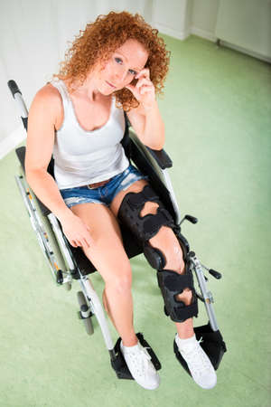recuperation: Woman in shorts and t-shirt seated in wheelchair with leg brace looks up at camera