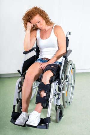 paraplegico: mujer joven con discapacidad abatido en una silla de ruedas con una pierna en un aparato ortopédico después de la cirugía de rodilla sentado mirando con tristeza a la baja