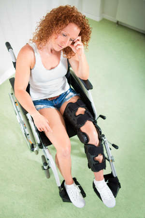 downhearted: Overhead view of sad woman in leg brace and shorts as she sits in a wheelchair