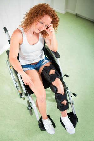 paraplegico: Vista de arriba de la mujer triste en la pierna ortopédica y pantalones cortos mientras se sienta en una silla de ruedas
