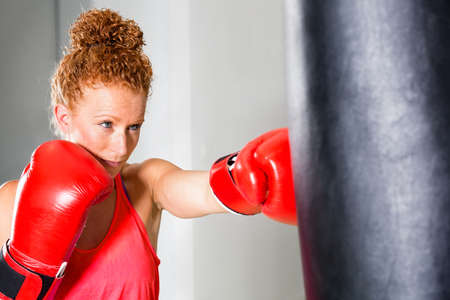 punched out: Determined young female boxer working out throwing punches at a punch bag with red leather gloves and a focused expression in a health and fitness concept