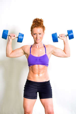 Strong muscular young woman lifting weights standing front on to the camera with a pair of dumbbells raised above her shoulders showing her toned abs and biceps