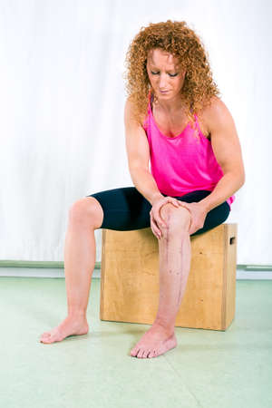 recuperation: Adult woman in long red curly hair rehabilitating injured leg by massaging the area while seated on crate indoors Stock Photo