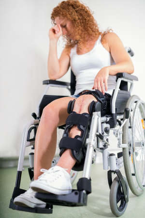 dejected: Dejected woman with her knee in a brace and a post-operative scar sitting in a wheelchair with her head resting on her hand in a disability and healthcare concept