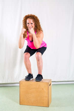 Smiling woman with long red curly hair performing squats on box. Scar from injury visible on shin. Stock Photo