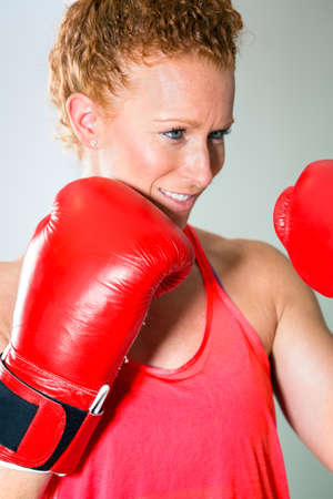 punched out: Close up of smiling female boxer in curly red hair tied up with gloves up and confident expression