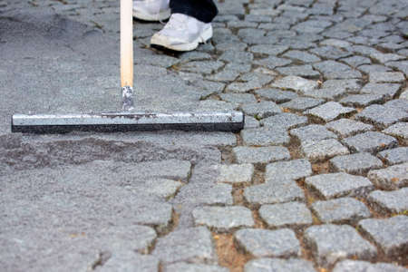 resurfacing: Worker resurfacing cobblestones sweeping gravel or mortar over the circular arrangement of stones to fill the gaps in a maintenance concept with a low angle view of the feet