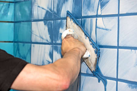 Workman or builder applying blue grout to white interior tiles in a house in a concept of DIY or decorating, close up view of his arm
