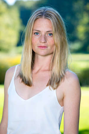 Woman in white blouse with calm expression and long shoulder length blond hair standing outside Stock Photo