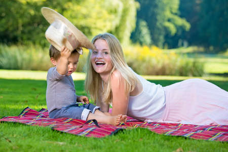 Curious child lifting up hat while woman laughs at him as they relax at park with blanket on grass