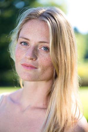 Gros plan sur beau sourire jeune adulte femme blonde avec des taches de rousseur debout à l'extérieur