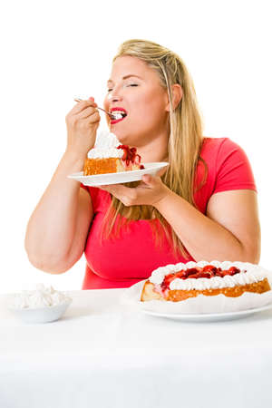 devouring: Obese young woman eating strawberry cream cakes on white