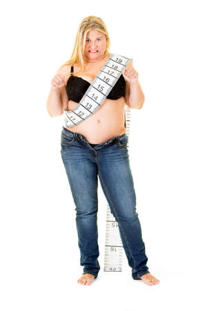 glandular: Fat overweight woman wearing a large tape measure standing in unzipped blue denim jeans and bra clenching her fists and gnashing her teeth, isolated on white Stock Photo