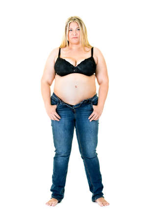 glandular: Overweight blond woman in a bra and unzipped jeans standing with her thumbs hooked in her pockets staring at the camera isolated on white
