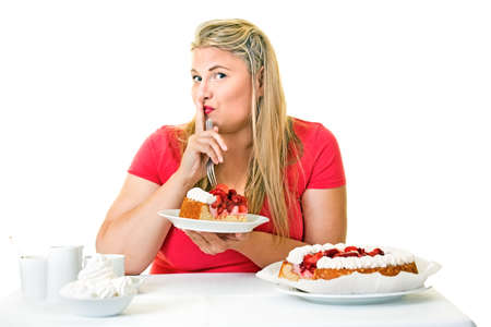 Guilty fat woman eating a slice of cream cake putting her finger to her lips in a hushing gesture asking the viewer to keep her secret
