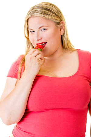 Smiling overweight blond woman eating ripe strawberry on white