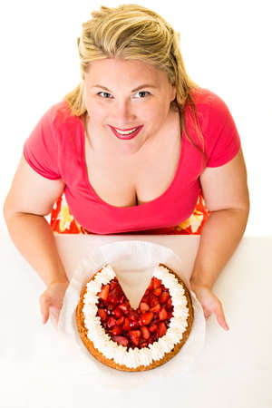 High angle view of happy overweight woman with cream cake missing slice