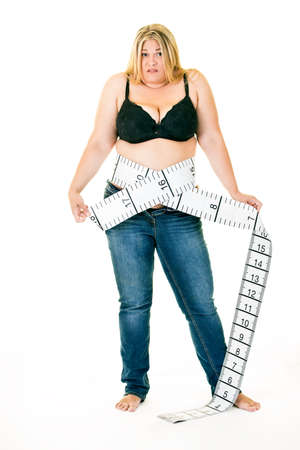Overweight young woman with large and long tape measure around waist Stock Photo