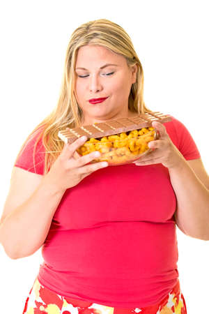 wry: Overweight young woman looking at bowl of unhealthy chips and chocolate
