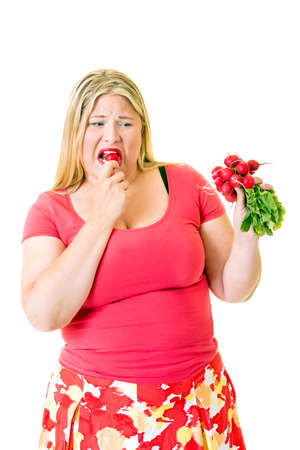 glandular: Overweight woman grimacing and eating healthy radishes on white