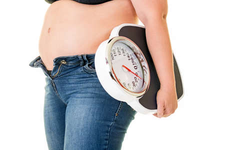 Fat overweight woman wearing unzipped blue denim jeans carrying a bathroom scale under her arm , side view close up on her stomach Stock Photo