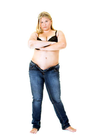 Overweight young woman in bra and jeans on white with folded arms